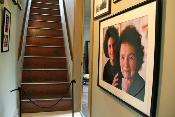 The two bedrooms above the Wyeth studio are closed to the public. The hallway leading to the stairs holds many family photographs, including this one of Andrew Wyeth's sister, Ann Wyeth McCoy and niece, Anna B. McCoy. (Emma Lee/for NewsWorks)