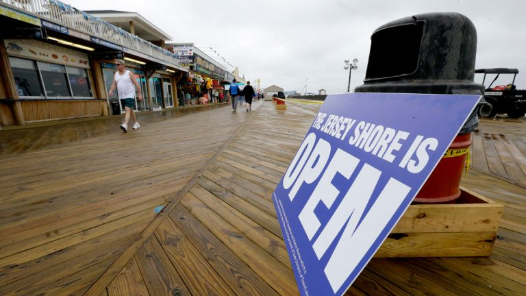 A sign rests on a trash can as people walk on the boardwalk, in Seaside Heights, The N.J. Business Association says business is down because potential visitors aren't aware that most of the restaurants have reopened. (AP Photo/Julio Cortez, file)