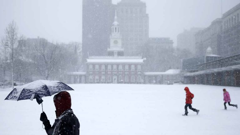 Pedestrians pass Independence Hall  in Philadelphia during a March storm. The city exceeded its snow removal budget by $1.2 million. (AP file photo)