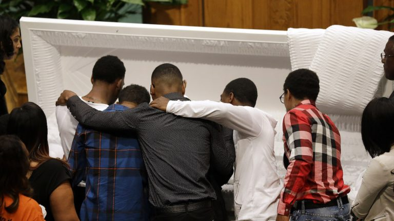 Mourners embrace as they gather in front of the casket containing the body of Freddie Gray before his funeral, Monday, April 27, 2015, at New Shiloh Baptist Church in Baltimore. Gray died from spinal injuries about a week after he was arrested and transported in a Baltimore Police Department van. (AP Photo/Patrick Semansky)