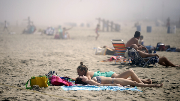 Sunbathers lay on the beach on a foggy afternoon in Belmar, N.J., ahead of the Fourth of July holiday. (Mel Evans/AP Photo, file)