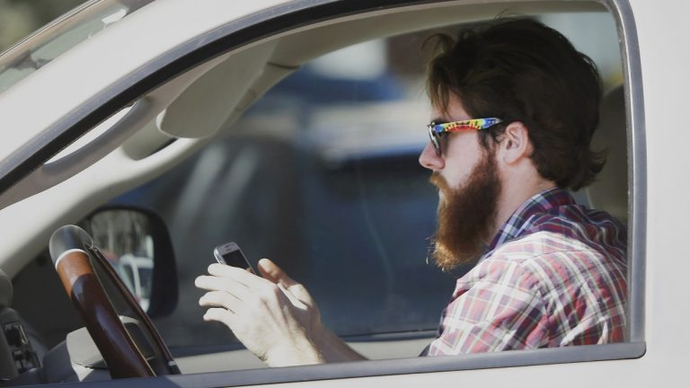 An man works his phone as he drives through traffic in Texas. Proposed legislation would allow police in New Jersey to search the cell phones of drivers involved in accidents to determine if they were texting or talking at the time of a crash. (AP Photo/LM Otero)
