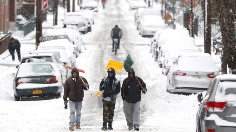 Men carry shovels as they walk on a snow covered road after a snowstorm in January in Hoboken, New Jersey. Gov. Chris Christie has proposed cutting the state's snow removal budget by half for next winters. (AP Photo/Julio Cortez)