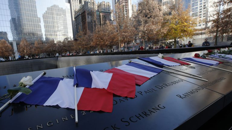 French flags rest on the engraved names at the 9/11 Memorial South Pool rim at the National September 11 Memorial and Museum following a tribute to victims of the Paris terrorist attacks. (Kathy Willens/AP)