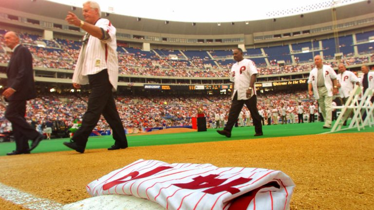 Former Philadelphia Phillies manager Dallas Green, second from left, follows former manager Paul Owens past a Pete Rose jersey which Green placed on first base, Rose's position, during ceremonies honoring the 1980 World Series championship team in 2000. Rose wasn't allowed to attend the ceremony. Green died Wednesday in  Philadelphia at the age of 82. (AP file photo)