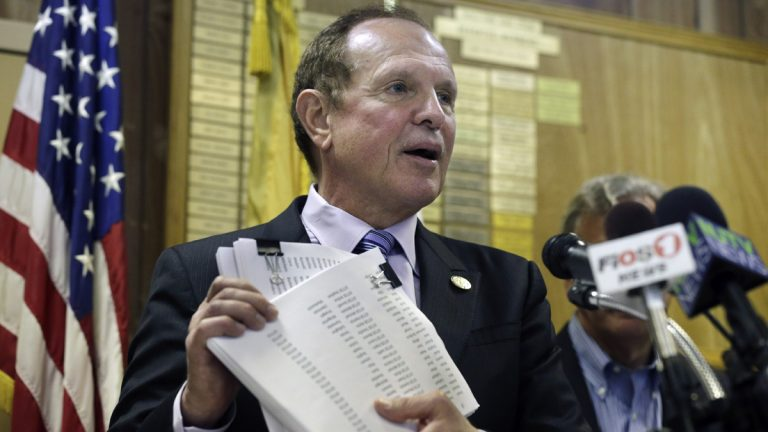 New Jersey Sen. Raymond J. Lesniak, D- Elizabeth, holds up petitions with more than 15,000 signatures against New Jersey Gov. Chris Christie's announced settlement with Exxon Mobil Corp. Lesniak called the Christie administration's proposed $225 million settlement of New Jersey's $8.9 billion claim for restoration of damage and destruction in the areas of Exxon Mobil's refineries in Linden, Bayonne and other facilities, the biggest corporate giveaway in New Jersey history. (AP Photo/Mel Evans)
