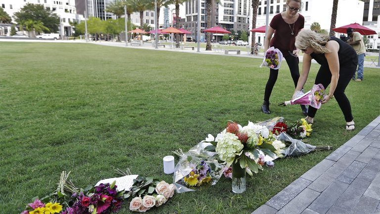 Two women place flowers for the victims of the fatal shootings at Pulse Orlando nightclub at a makeshift memorial Monday