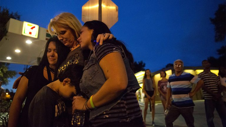 Elsie Allen, center, huddles with her daughters Jenna Allen, right, and Krista Allen-Parra, left, and her grandson Shawn Flores, all of Orlando, as they visit for the first time the scene of the Pulse nightclub mass shooting from a block away Friday, June 17, 2016, in Orlando, Fla. (AP Photo/David Goldman)
