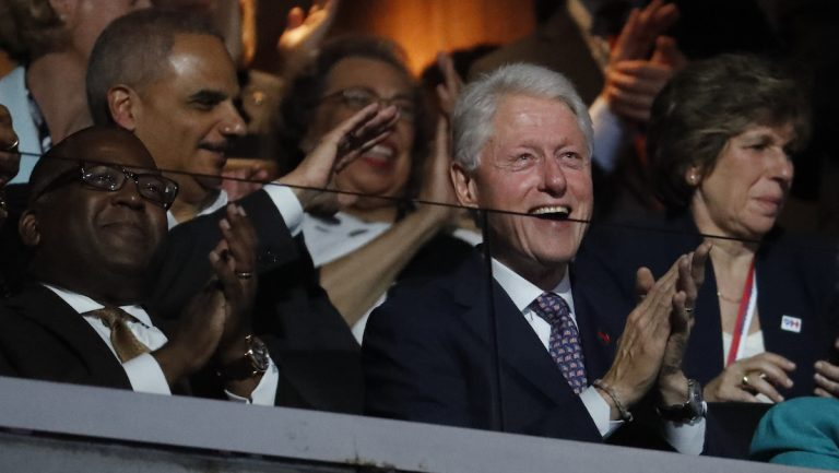 Former President Bill Clinton applauds as First Lady Michelle Obama speaks during the first day of the Democratic National Convention in Philadelphia