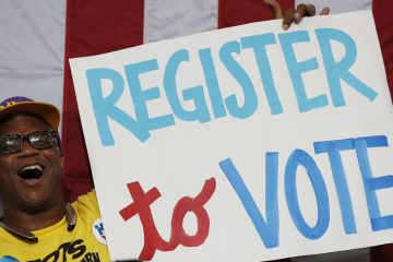 In this file photo a man in the audience cheers as he holds up a sign during a voter registration event at West Philadelphia High School (Carolyn Kaster/AP Photo)