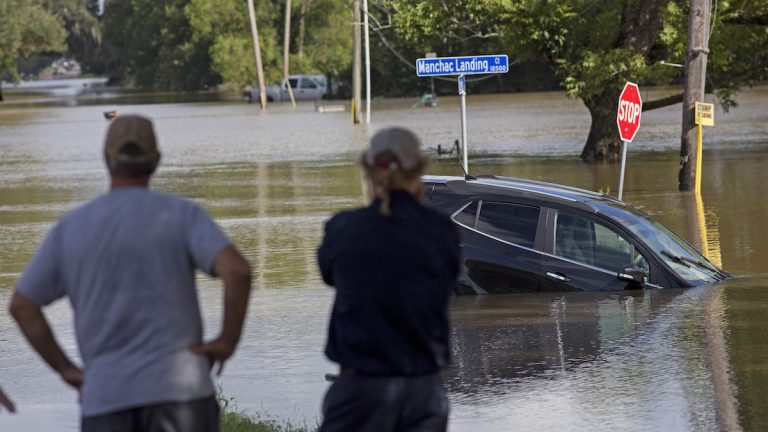 Prairiesville, Louisiana,  residents last month survey the flood water on Old Jefferson Highway. The flooding killed at least 13 people, damaged 150,000 homes and cost at least $8.7 billion. (AP Photo/Max Becherer, File)
