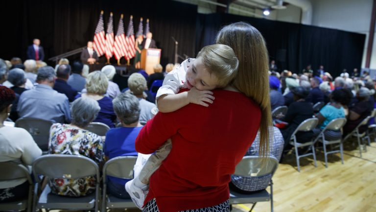 A woman holds her child as Republican presidential candidate Donald Trump delivers a policy speech on child care, Tuesday, Sept. 13, 2016, in Aston, Penn. (AP Photo/Evan Vucci)