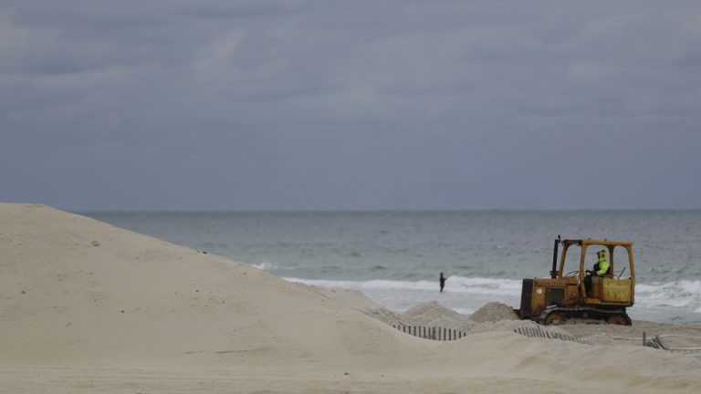 A worker pushes sand onto a protective sand dune in Seaside Heights