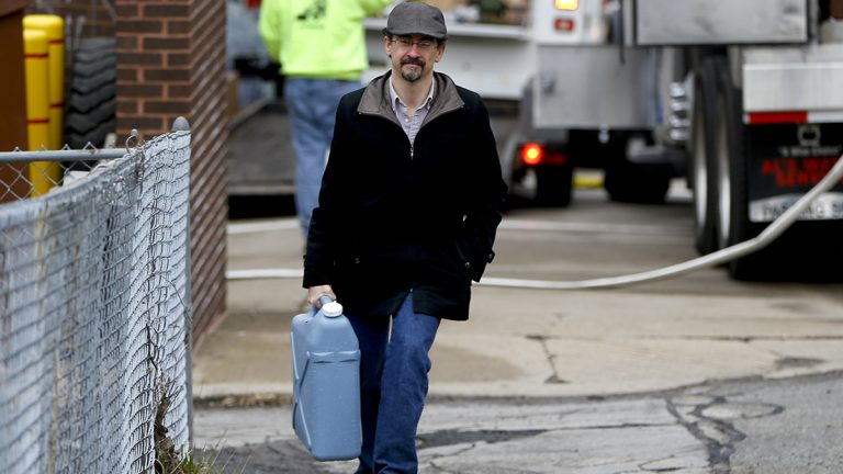 Tim Stuhldeher carries a container of water after filling it at a fire station in Pittsburgh's Lawrenceville neighborhood on Feb. 1, 2017. After the state's Department of Environmental Protection found low levels of chlorine at a city water facility, the subsequent flush-and-boil advisory affected 100,000 customers. Pittsburgh Mayor Bill Peduto announced on Wednesday that as Pittsburgh updates its aging water infrastructure, all city residents will receive a water filter. (AP Photo/Keith Srakocic)