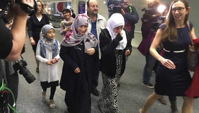 Eman Ali, 12, second from left, walks with her father, Ahmed Ali, center, after they arrived at San Francisco International Airport, Sunday, Feb. 5, 2017, in San Francisco. Joining them is her sister Salma Ali, 14, second from right, her cousin, left, who is unidentified, and their lawyer Katy Lewis, at right. Eman and her father were stuck for a week in Dijbouti after President Donald Trump signed an executive order temporarily banning people from seven predominantly Muslim nations from entering the United States. (AP Photo/Olga Rodriguez)