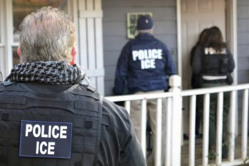 In this file image, U.S. Immigration and Customs Enforcement agents arrive at a home during a targeted enforcement operation.  (Bryan Cox/ICE via AP)