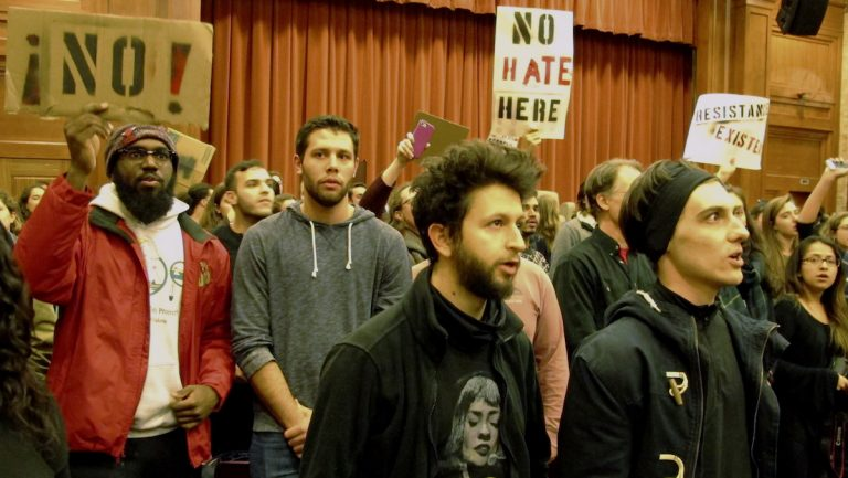 Middlebury College students turn their backs to Charles Murray, unseen, during his lecture in Middlebury, Vt., Thursday, March 2, 2017. Hundreds of college students protested his lecture, forcing the college to move his talk to an undisclosed campus location from which it was live-streamed to the original venue. He still could not be heard above protesters' chants, feet stamping and occasional smoke alarms. (AP Photo/Lisa Rathke)