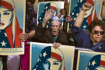 FILE - In this Feb. 19, 2017 file photo, people carry posters during a rally against President Donald Trump's executive order banning travel from seven Muslim-majority nations, in New York's Times Square. (AP Photo/Andres Kudacki, File)