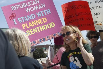 In this Wednesday, March 22, 2017 photo, Carolyn Williamson waves a placard in support of Planned Parenthood as she joins other protesters against the failed Republican health care act in a demonstration outside the office of U.S. Rep. Ken Buck in Castle Rock, Colo. (AP Photo/David Zalubowski)