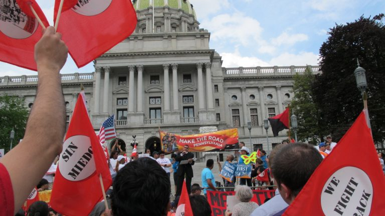 Demonstrators gather with more than 200 others  at a May Day rally on the steps of the Pennsylvania Capitol Monday in Harrisburg, Pennsylvania. Speaking is the Rev. Gregory Edwards of Allentown. (AP Photo/Marc Levy)