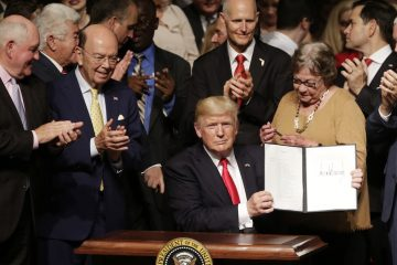 President Donald Trump shows the signed executive order surrounded by cabinet members and supporters in Miami, Friday, June 16, 2017. Trump announced a revised Cuba policy aimed at halting the flow of U.S. cash to the country's military and security services while maintaining diplomatic relations. From left are, Agriculture Secretary Sonny Perdue, Commerce Secretary Wilbur Ross, the president, Florida Gov. Rick Scott, Cary Roque, a Cuban political dissident, and Vice President Mike Pence. (AP Photo/Lynne Sladky)