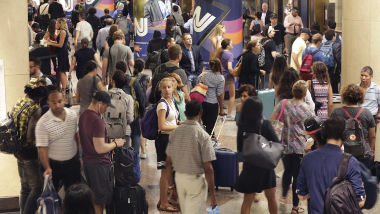 Passengers navigate the New Jersey Transit area in New York's Penn Station Tuesday. New Jersey Transit says some trains have been canceled this week because engineers are choosing not to work under the terms of their contract amid the summer-long repair work at Penn Station. (AP Photo/Richard Drew)