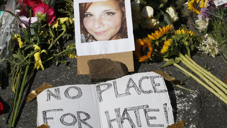 A makeshift memorial of flowers and a photo of victim, Heather Heyer, sits in Charlottesville, Va., Sunday, Aug. 13, 2017. Heyer died when a car rammed into a group of people who were protesting the presence of white supremacists who had gathered in the city for a rally. (AP Photo/Steve Helber)