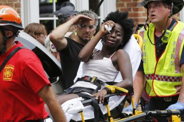 Rescue personnel help an injured woman after a car ran into a large group of protesters after an white nationalist rally in Charlottesville, Va., Saturday, Aug. 12, 2017. (AP Photo/Steve Helber)