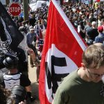 This Saturday, Aug. 12, 2017 image shows a white supremacist carrying a Nazi flag into the entrance to Emancipation Park in Charlottesville, Va. (Steve Helber/AP Photo)