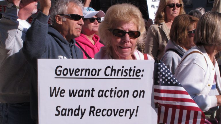 A woman holds a sign calling on New Jersey Gov. Chris Christie to help victims of Superstorm Sandy during a protest rally outside the New Jersey Statehouse in May. (Wayne Parry/AP Photo)
