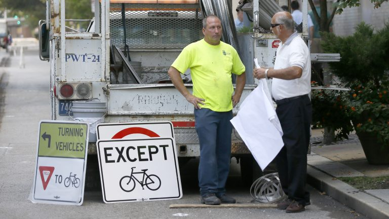Public works employees prepare to change signs along the eastbound lane of Penn Ave. in downtown Pittsburgh, Pa. on Wednesday, Sept. 3, 2014. City officials closed the eastbound lane from 6th Street in downtown to 16th Street in the city's Strip District to motor vehicles and made it a protected bicycle lane. (AP Photo/Keith Srakocic)