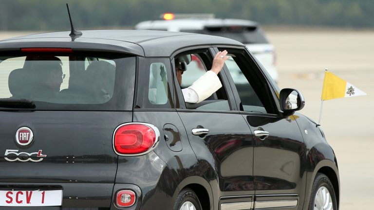 Pope Francis waves from a Fiat 500 as his motorcade departs from Andrews Air Force Base. (Andrew Harnik/AP Photo)