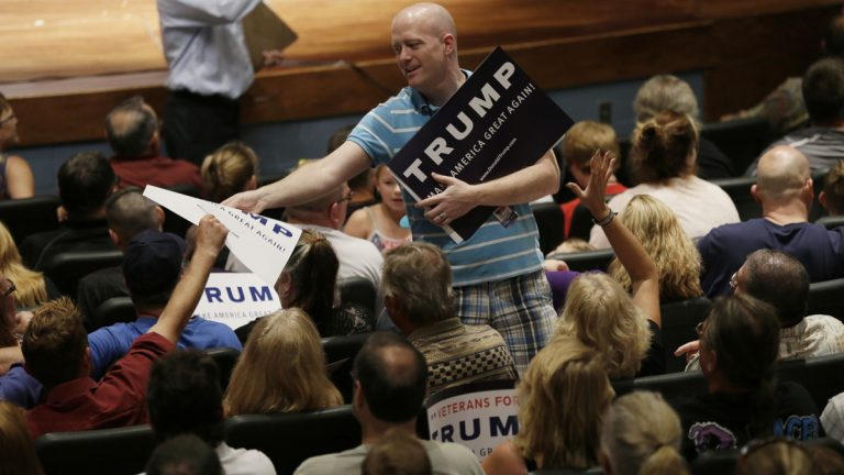 A volunteer passes out campaign signs for Republican presidential candidate Donald Trump at a rally and picnic last month in Oskaloosa, Iowa. (AP Photo/Charlie Neibergall)