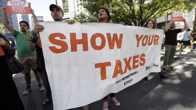 Protestors march in a downtown street holding a sign in support of Republican presidential candidate Donald Trump releasing his tax returns