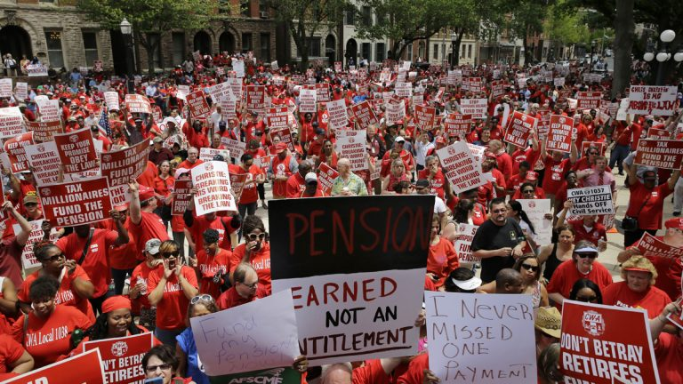 Public employee union members fill the plaza and street in front of the New Jersey Statehouse last year to protest Gov. Chris Christie's pension funding reductions. A conservative think tank says the state's health benefits for retirees is a bigger problem than its pension obligations. (AP file photo)