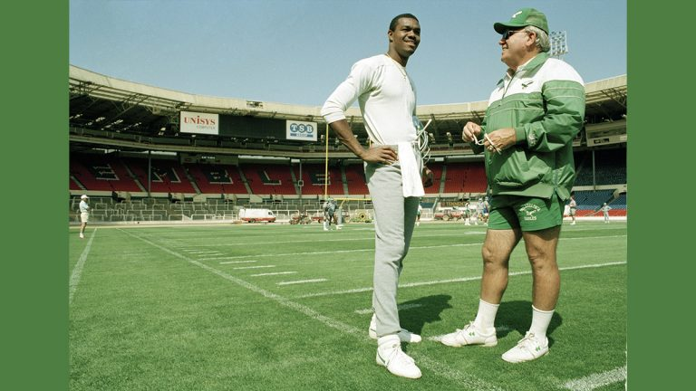 Randall Cunningham, quarterback for the Philadelphia Eagles talks with head coach Buddy Ryan during a light training session, Aug. 5, 1989, at London's Wembley Stadium where they took on the Cleveland Browns for the 1989 American Bowl. (AP Photo/Gillian Allen)