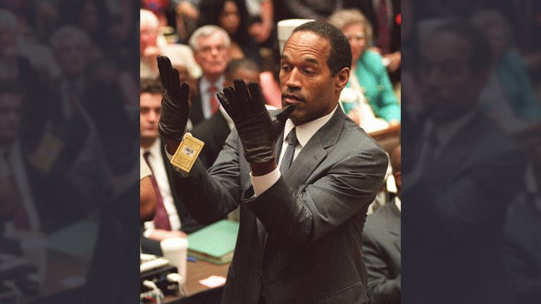 O.J. Simpson holds up his hands before the jury after putting on a new pair of gloves similar to the infamous