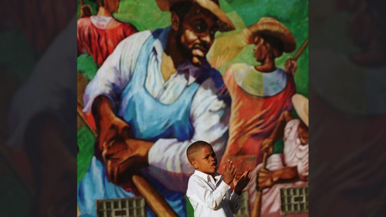 Marlin Hardy, 5, claps to get the attention of teachers as the field hands in the mural