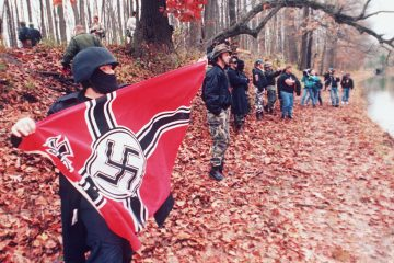 An unidentified member of a neo-Nazi group displays a Nazi battle flag by the Delaware Canal as others engage in a shouting match with opponents on the other side of the canal during an anti-gay rally last year in a state park in Washington Crossing, Pennsylvania. Both groups also hurled rocks, bottles, and sticks at one another as hundreds of state police stood by. (AP Photo/Widman)