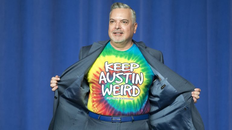 DNC Finance Chairman Henry Munoz, opens up his suit jacket to reveal his 'Keep Austin Weird' tie-dye t-shirt, on stage before introducing President Barack Obama at DNC fundraiser at the Austin Music Hall in Austin, Texas, Friday, March 11, 2016. (Pablo Martinez Monsivais/AP Photo)
