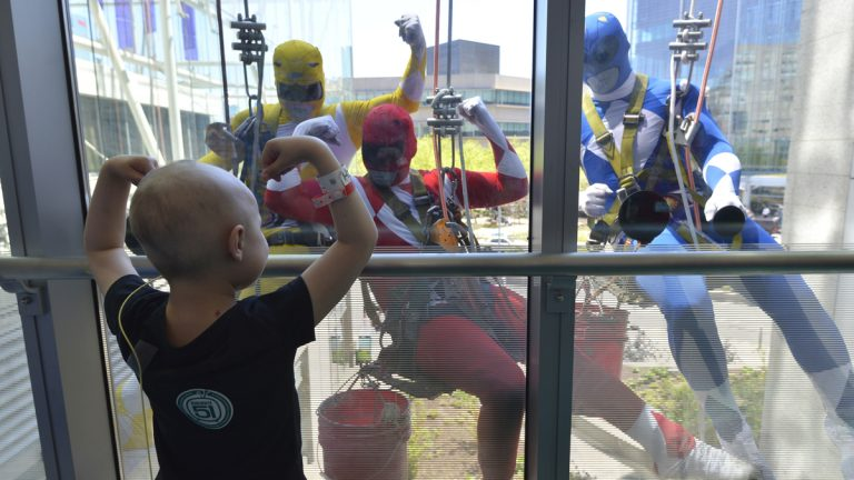 A patient at the Children's Hospital of Philadelphia flexes her muscles for window washers dressed up as Power Rangers on Tuesday, April 18, 2017. (HSE Photography/CHOP Photo)