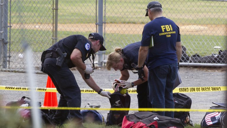 An FBI Evidence Response team inspects the contents of one of the many bags left at the scene of a shooting in Alexandria, Va., Wednesday, June 14, 2017, involving House Majority Whip Steve Scalise of La., and others, during a congressional baseball practice. (Cliff Owen/AP Photo)