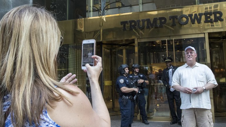 In this Thursday, Aug. 10, 2017 photo, a man poses for a photo in front of heavily armed police officers standing guard outside Trump Tower in New York. Donald Trump plans to come home to Trump Tower for a few days starting Sunday, the first time since his inauguration. New York City police are planning a slight security clampdown in the area around the skyscraper for the duration of his visit. (Mary Altaffer/AP Photo)