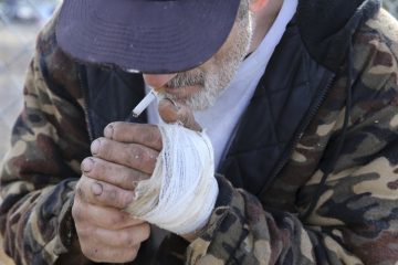 In this Thursday, Oct. 29, 2015 photograph, Jim 'Woods' Ellis lights the stub of a cigarette as he stands in an industrial area of Camden, N.J. Woods describes using the drug, naloxone, often known by the brand name Nacran, to reverse a heroin overdose. (Mel Evans/AP Photo)