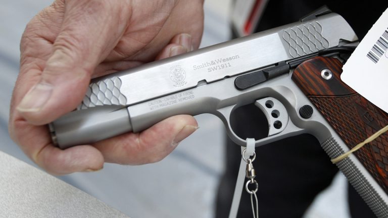 An exhibitor displays a .45 cal Smith & Wesson pistol. (Keith Srakocic/AP Photo)
