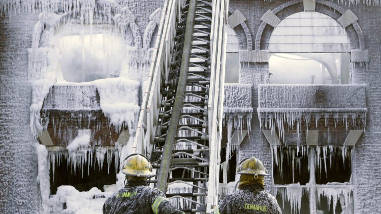 Philadelphia firefighters work the scene of an overnight blaze in West Philadelphia Monday as icicles hang from where the water from their hoses froze. (Jacqueline Larma/AP Photo)