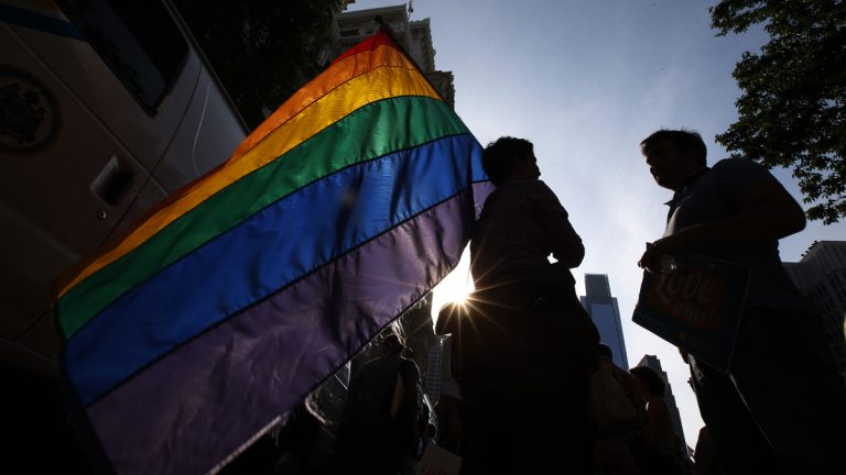 A person holds a rainbow-colored gay pride flag during a rally at Philadelphia City Hall in May 2014, following the overturning of the ban on same-sex marriage in Pennsylvania by a federal judge. (AP Photo/Matt Slocum)