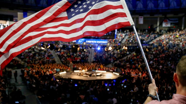 A man in the audience waves an American flag at Liberty University (Andrew Harnik/AP Photo)