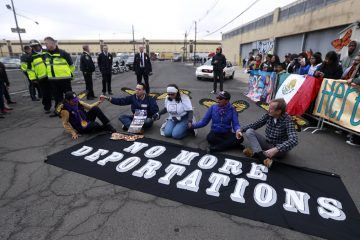 Activists block a street as police officers look on during an immigration protest outside of a detention center, Thursday, Feb. 23, 2017, in Elizabeth, N.J. The activists were taken into custody after they refused to clear the street. (Julio Cortez/AP Photo)
