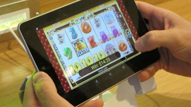 A person plays a slot on a touch-screen tablet